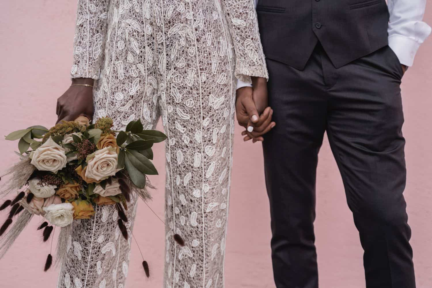 A bride in a lace jumpsuit is posed beside a groom in a gray suit. They are pictured from the waist-down in front of a pink wall.