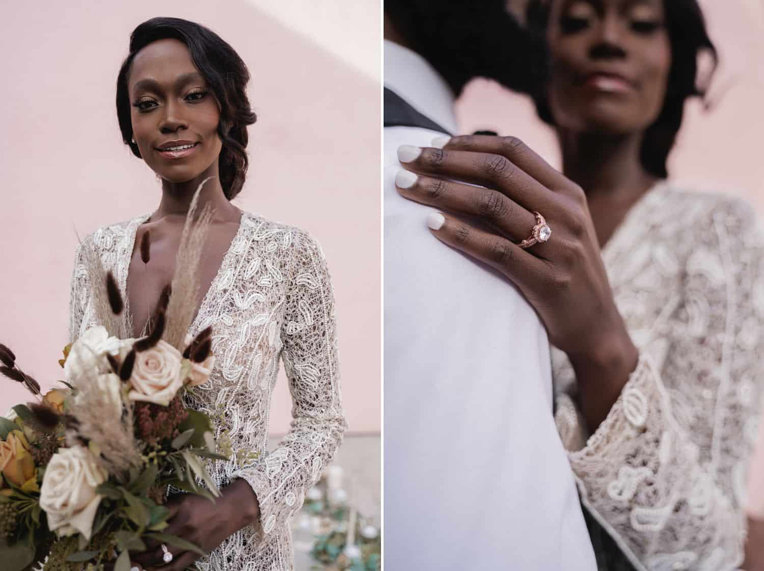 A Black bride in a lace jumpsuit stands in front of a pink wall with a stunning diamond engagement ring and a large bouquet of flowers.