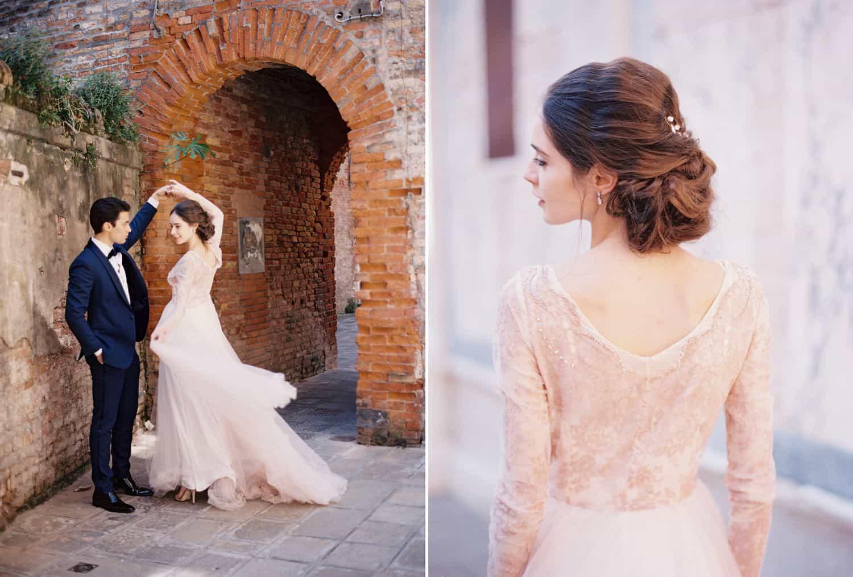 A groom in a blue tuxedo twirls a bride in a pink wedding dress in an Italian alleyway.