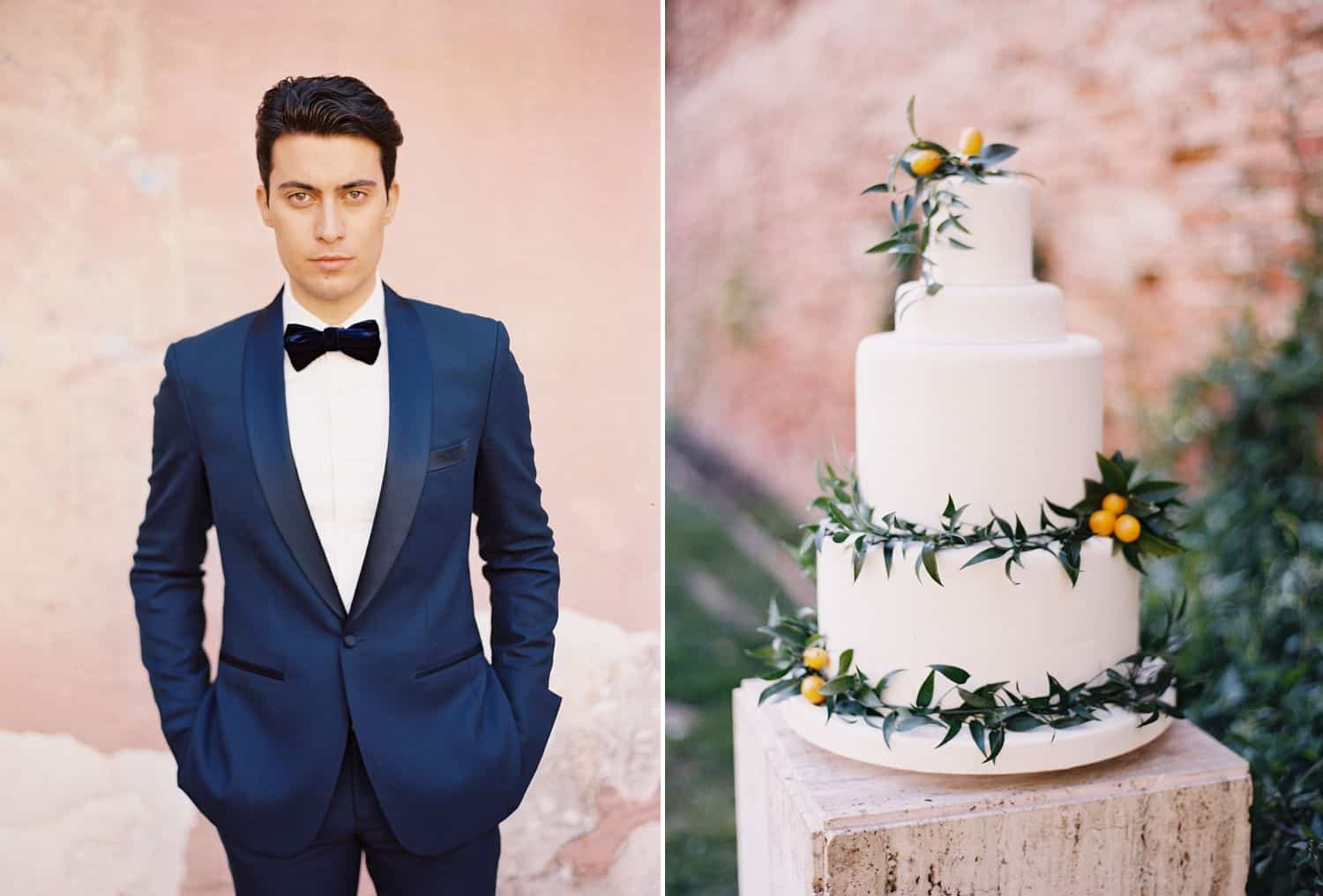 A groom in a blue tuxedo and black bow tie stands next to a tiered wedding cake, all in front of a pink wall.