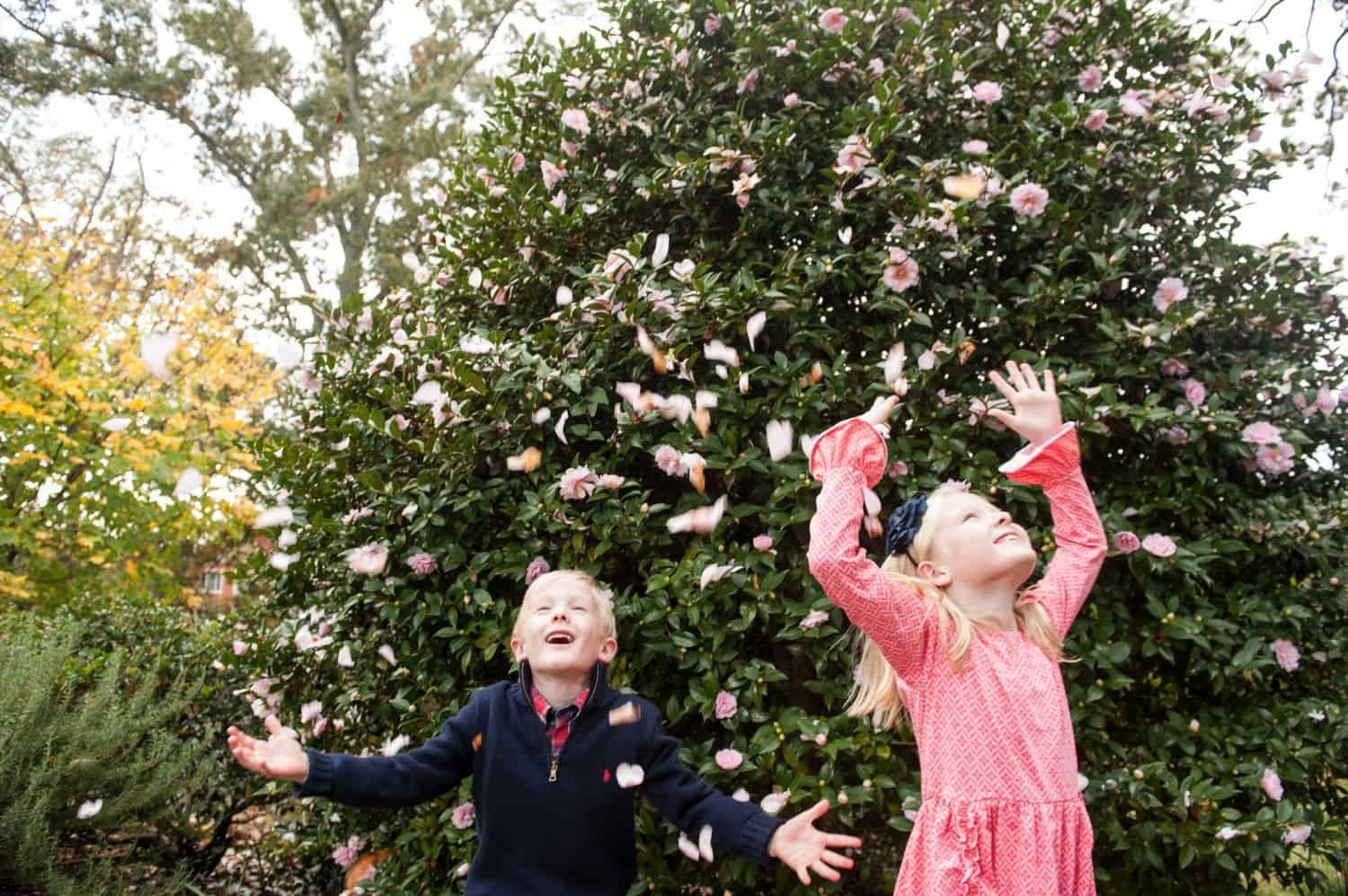 A brother and sister throw pink flower petals into the air.