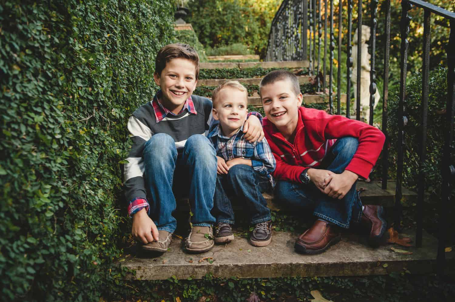 Three brothers sit together in concrete steps surrounded by ivy.
