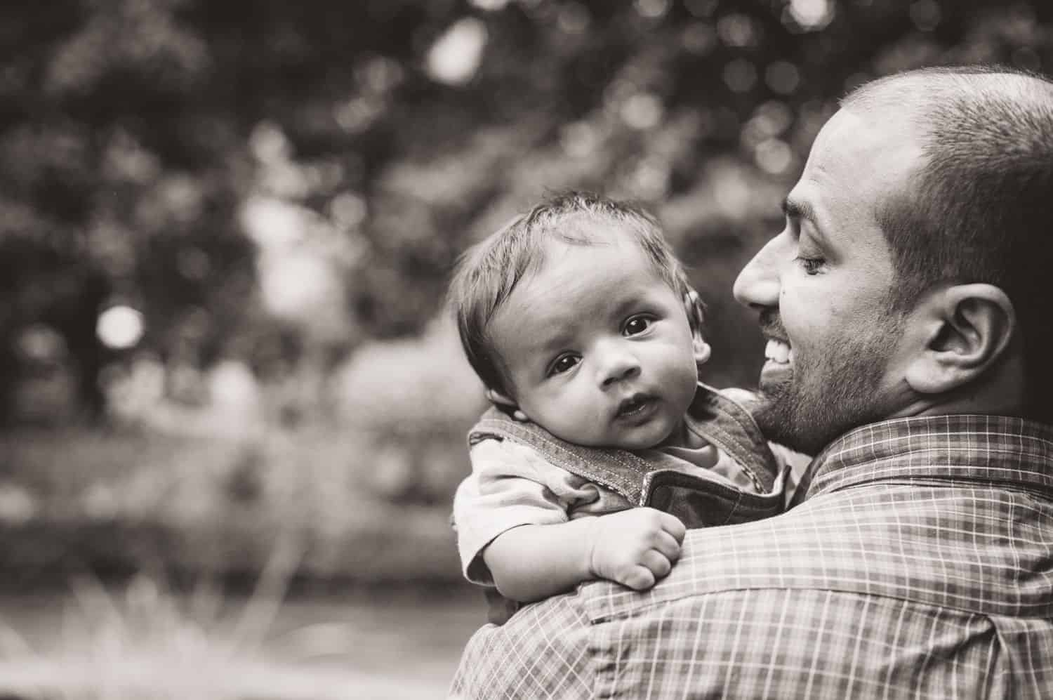 A dad snuggles his toddler son close to his face in black and white.