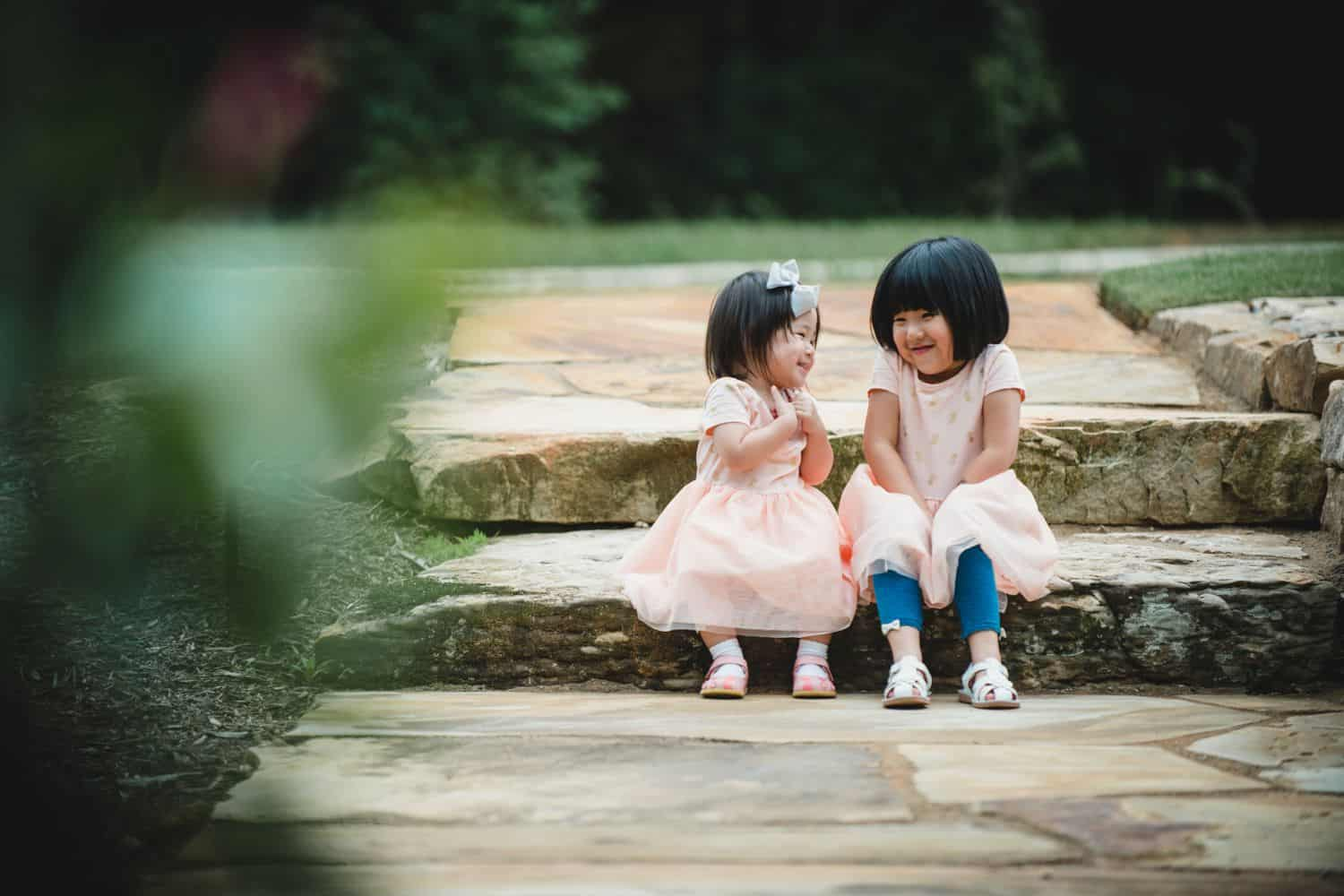 Two little girls sit on stone steps in pink dresses.