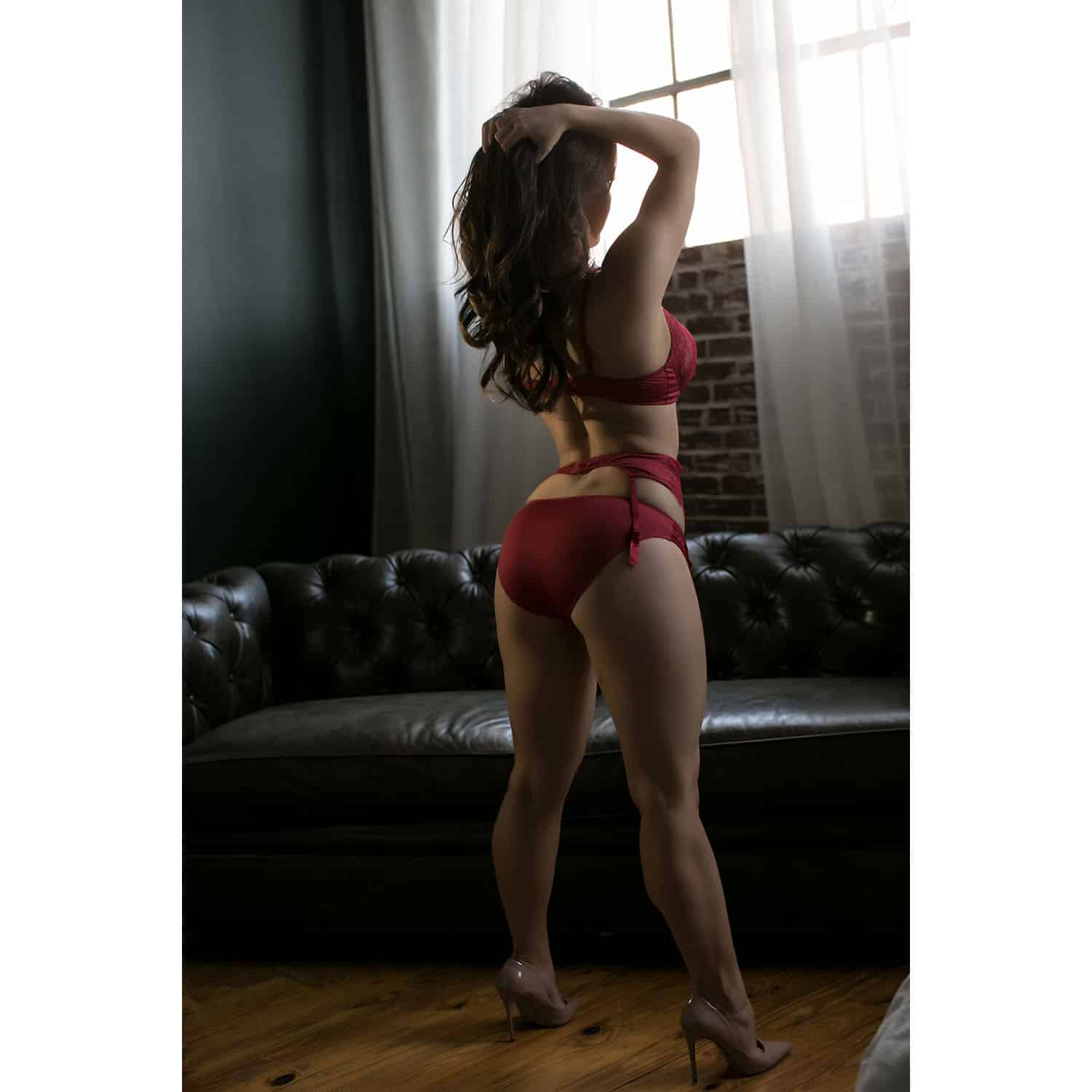 OWN Boudoir's portrait of a woman posing in red lingerie while looking out a window