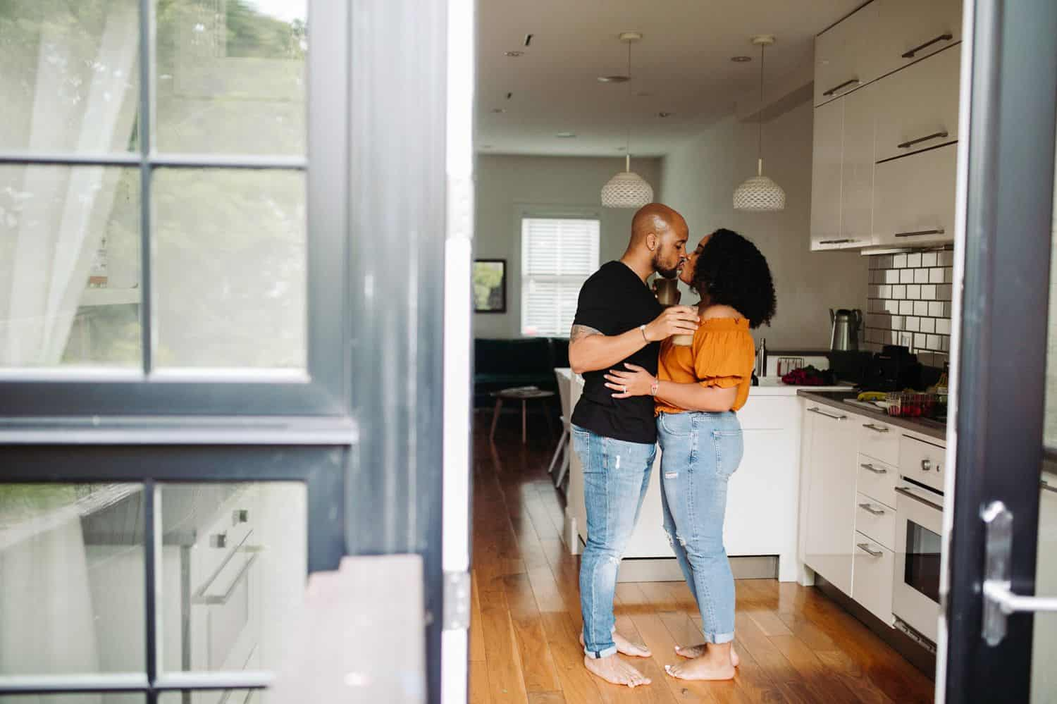 A Black couple stands in the kitchen of their Atlanta Airbnb where they've hired Kiyah C. to make their portraits