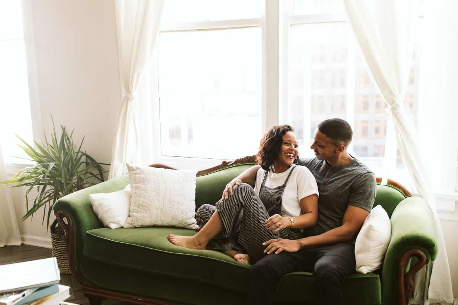 A Black couple sits on the vintage green couch that sits before a bright window in their Atlanta Airbnb