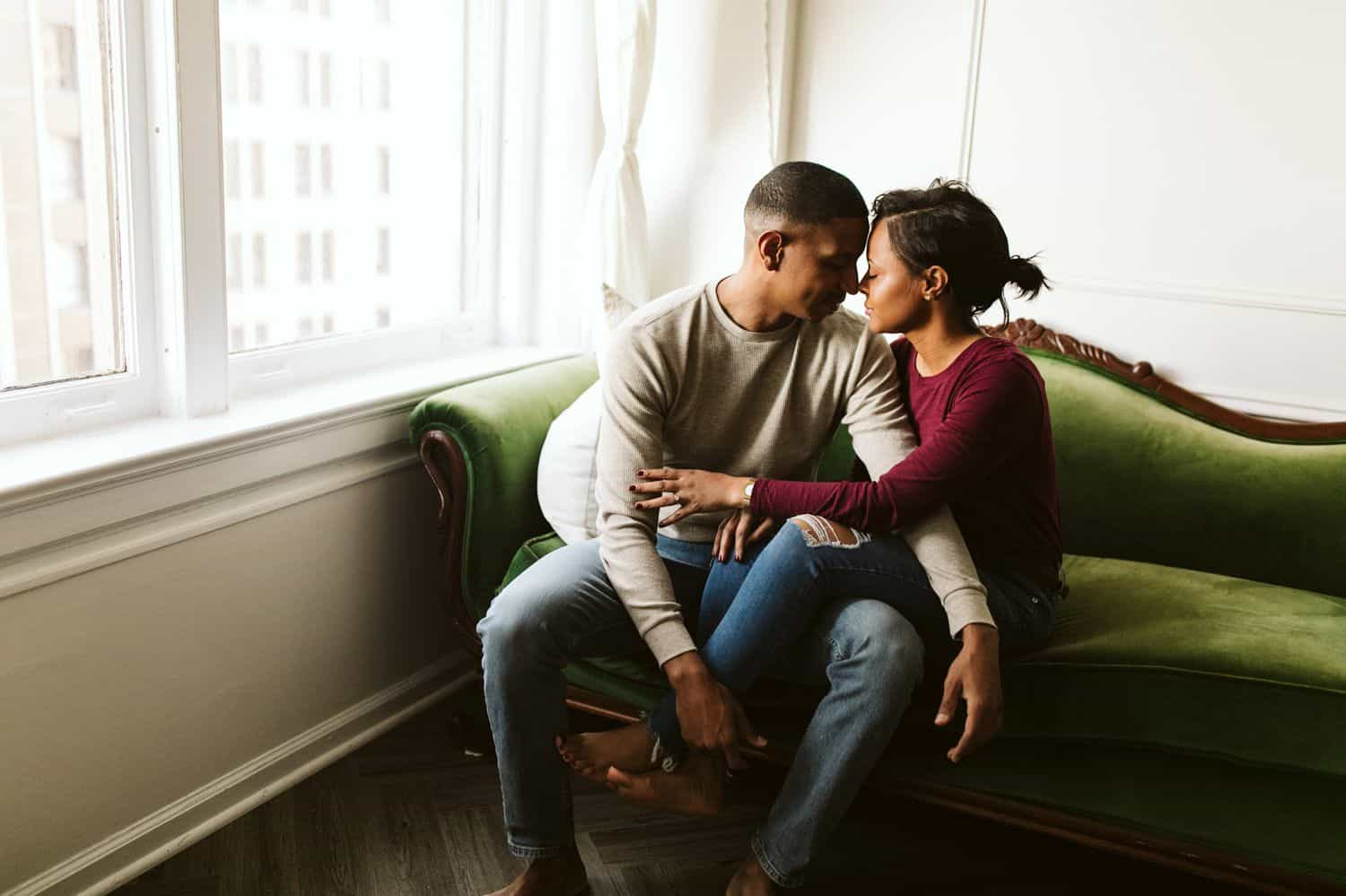A Black couple snuggles on the vintage green sofa in their Atlanta Airbnb