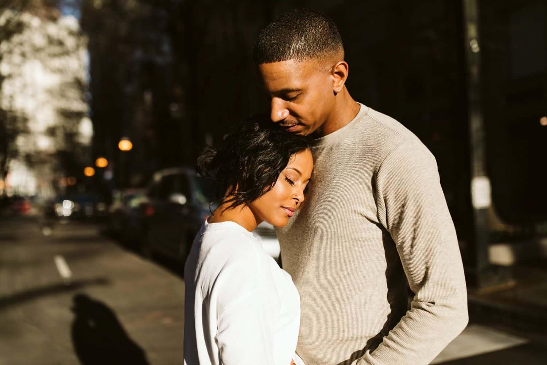 A Black couple enjoys the warm sun shining in a city street outside their Atlanta Airbnb
