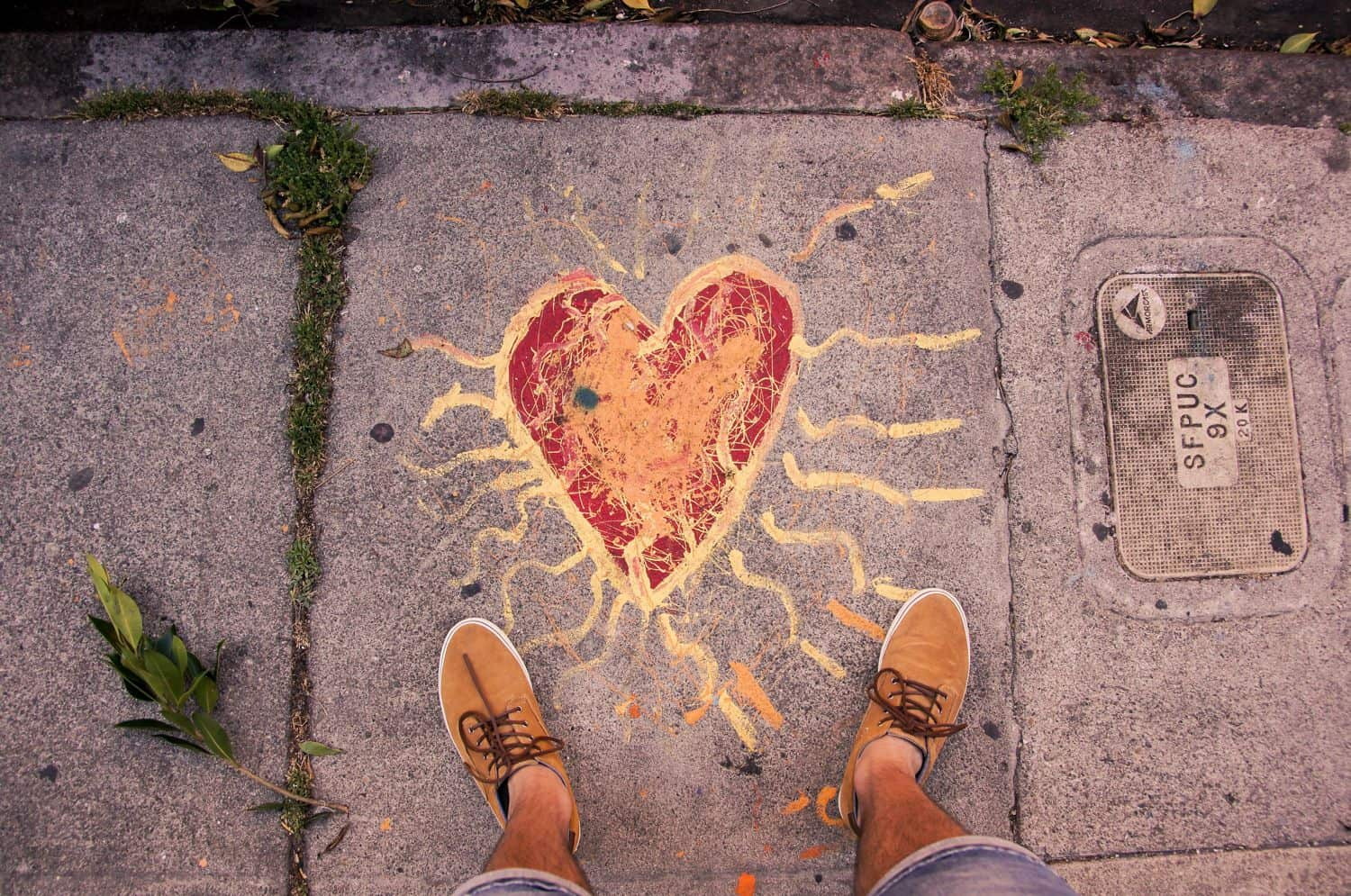 From above, a pair of feet stand on either side of a flaming heart drawn in sidewalk chalk.