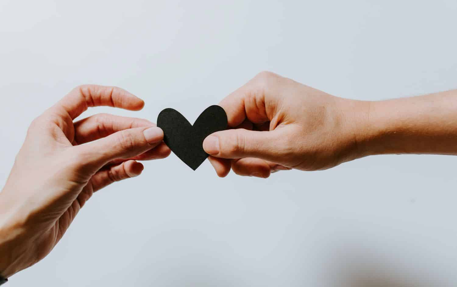 A person hands a paper heart to another person in front of a white backdrop.