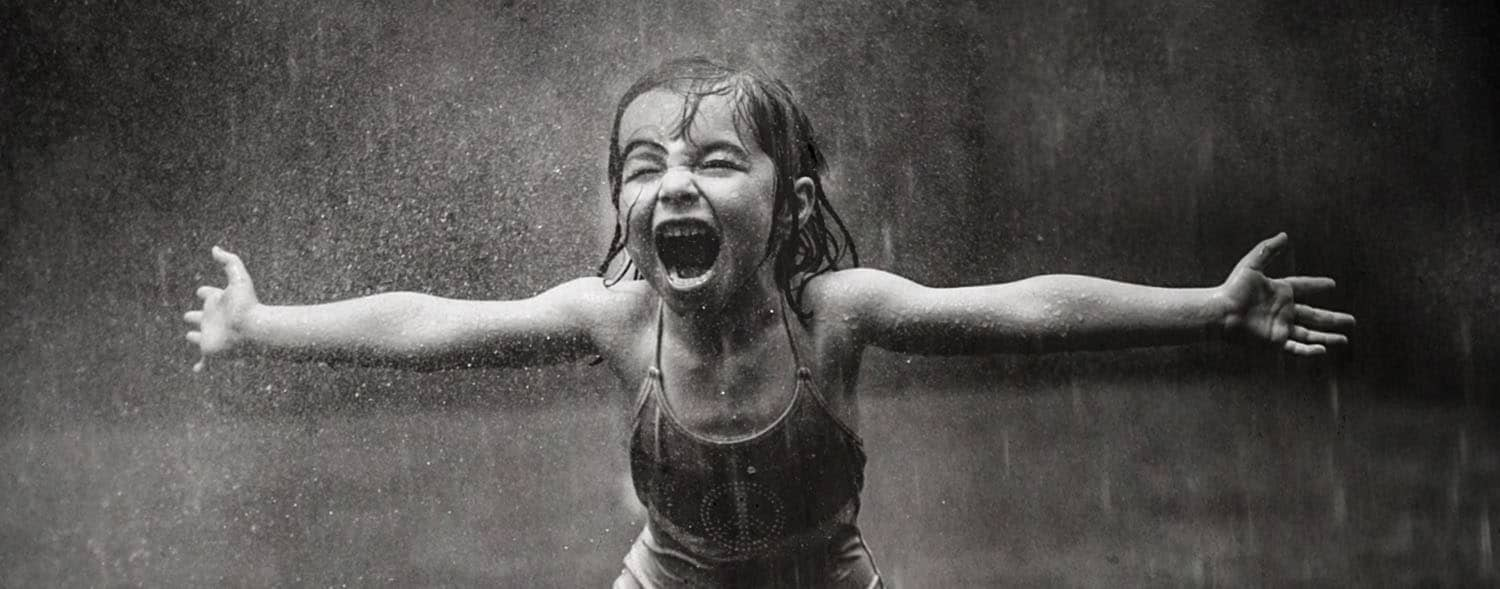 Black and white photo of a little girl in a one-piece bathing suit. She stands in the pouring rain with her arms spread wide. She appears to be yelling with joy.