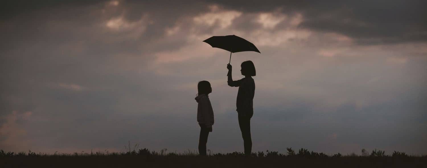 An adult holds an umbrella over a child beneath a stormy sky.