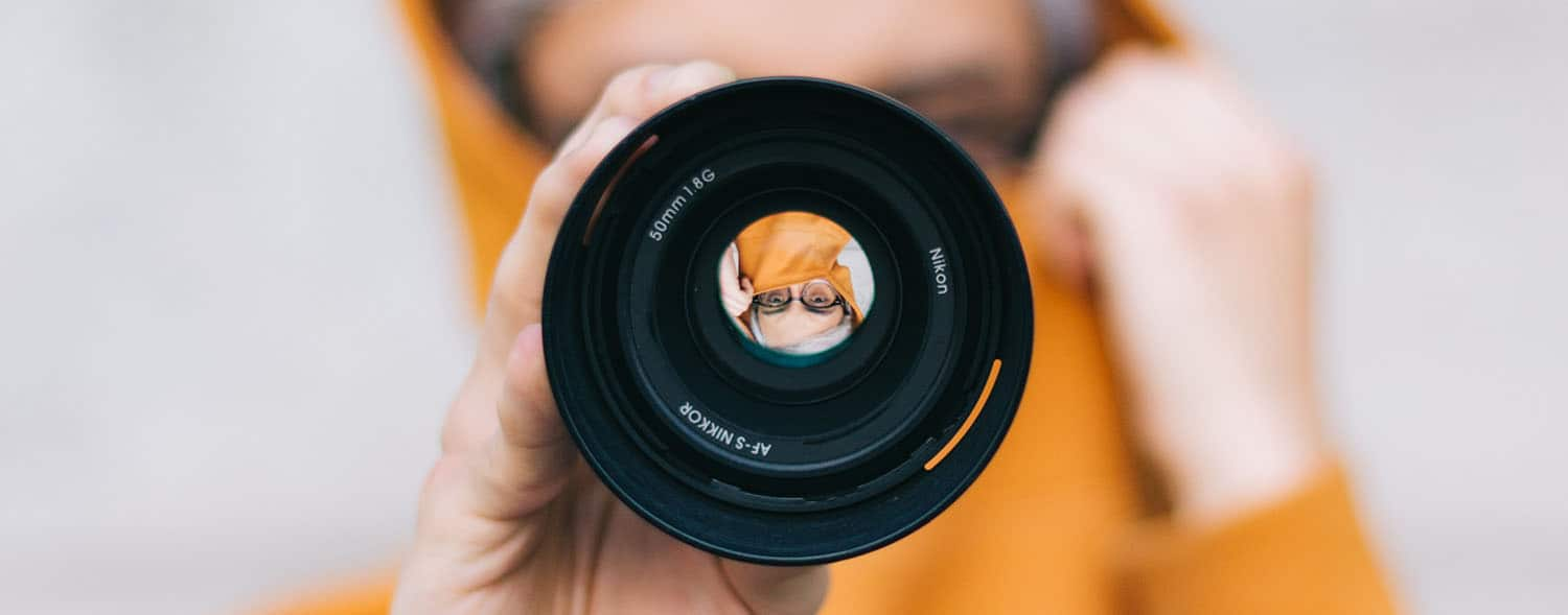 A person in an orange hoodie holds a lens in front of their face.
