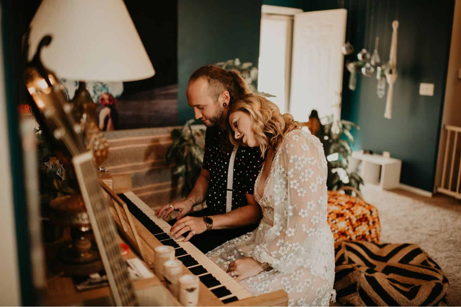 A couple sits at a piano in their eclectically decorated home. The woman's head rests on the man's shoulder as he plays. Learn how to take low light photos like this one by Shelby Laine Photography.