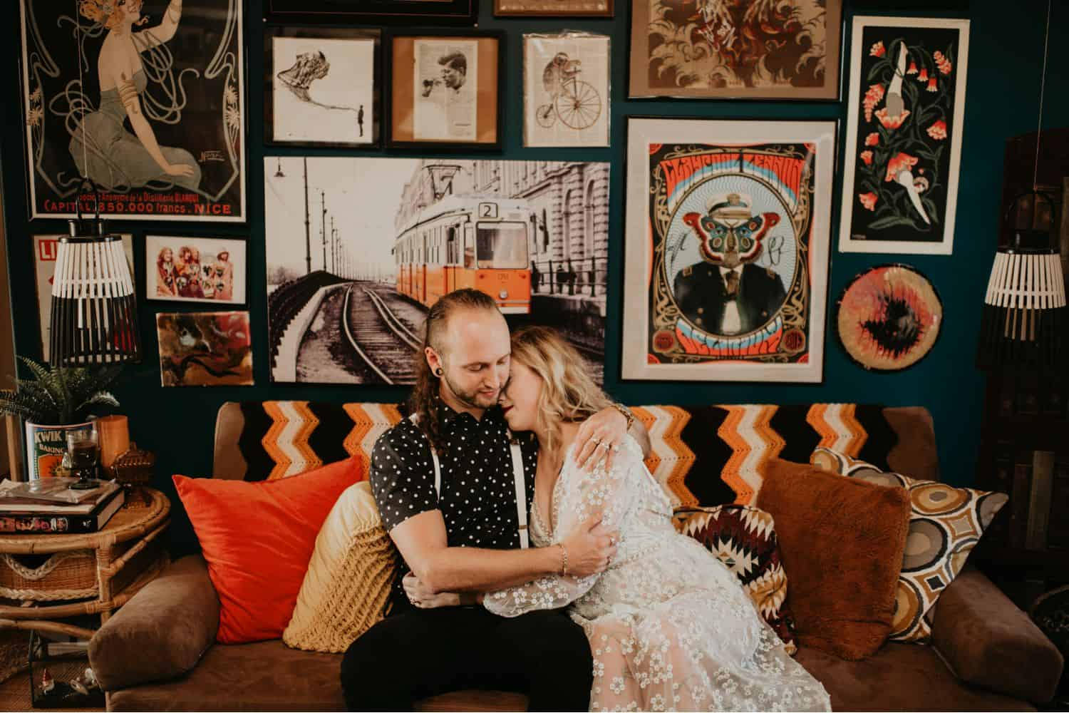 A couple embraces on their sofa. The wall behind them is covered in framed artwork. Learn how to take low light photos like Shelby Laine Photography