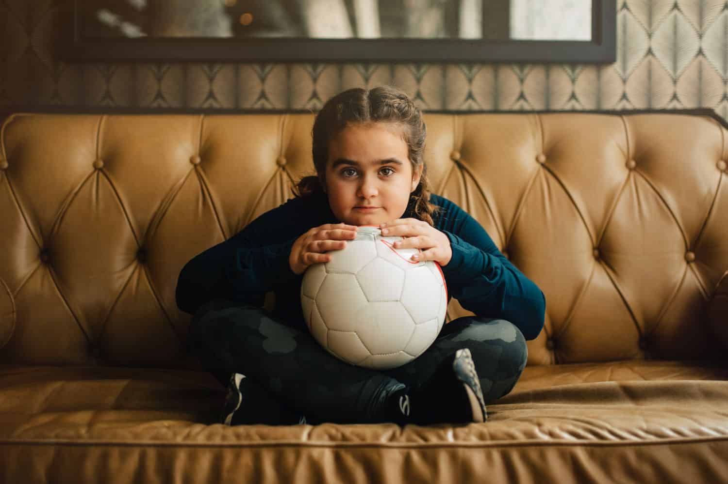 A little girl with French braids sits cross-legged on a leather sofa holding a soccer ball in her lap. By Kate T. Parker for Strong is the New Pretty