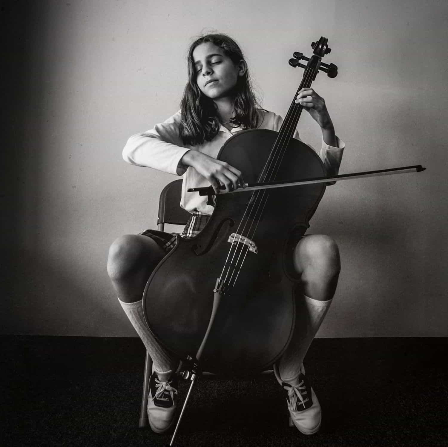 Black and white photograph of a young girl playing the cello. By Kate T. Parker for Strong is the New Pretty