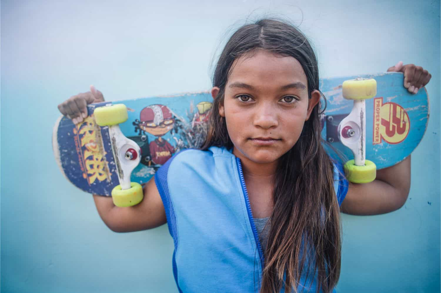 A girl with long messy hair holds a skateboard across her shoulders and gazes directly into the camera. By Kate T. Parker for Strong is the New Pretty