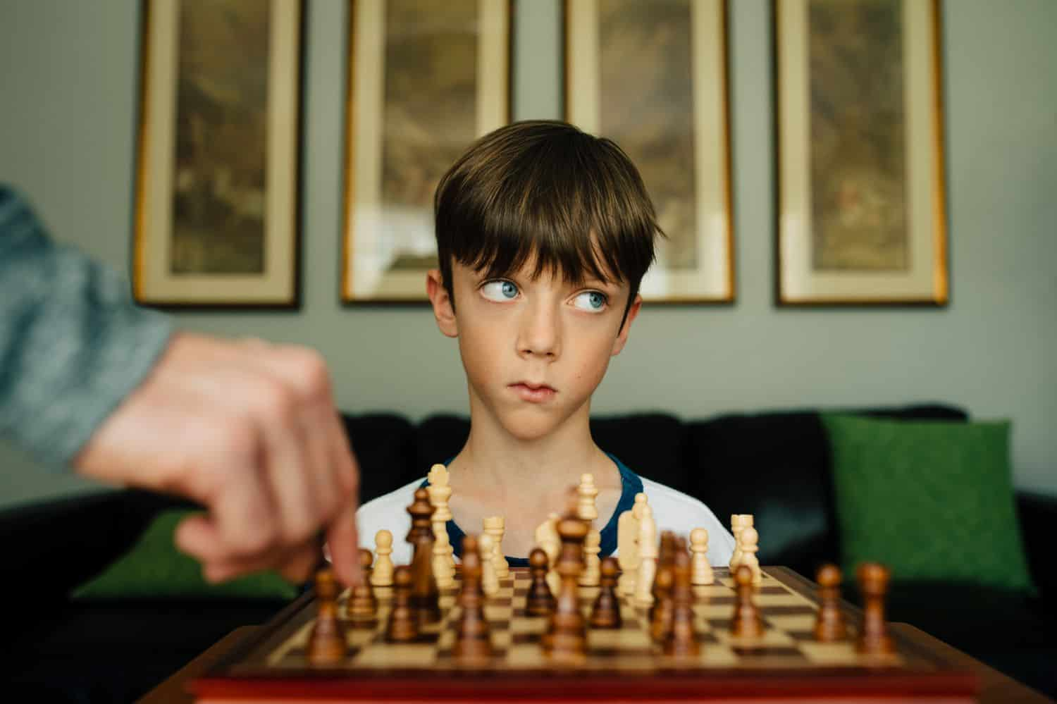A little boy sits at a chess set rolling his eyes. By Kate T. Parker for The Heart of a Boy