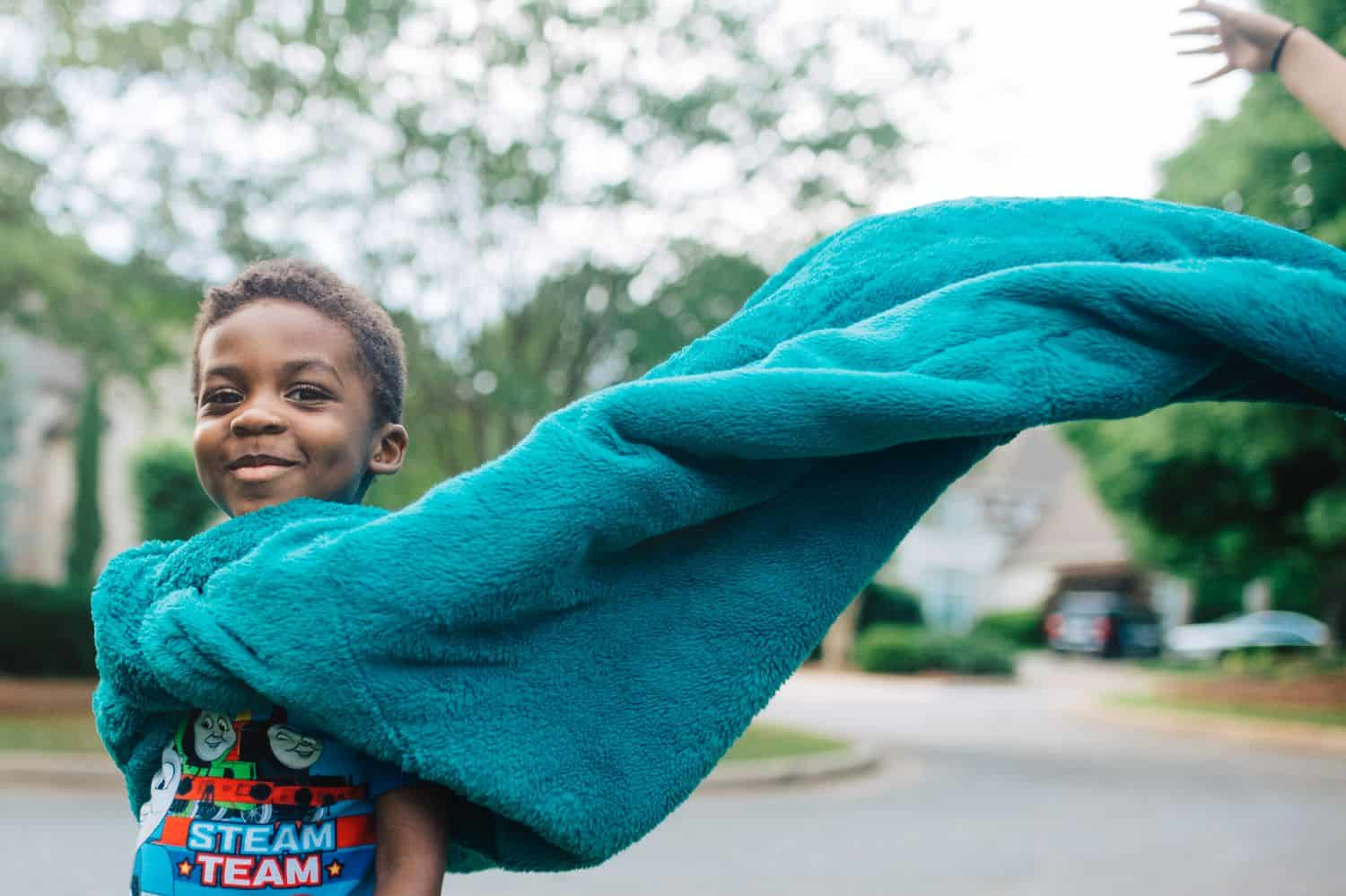A little boy wears his blue bedspread as a cape. Photo by Kate T. Parker for The Heart of a Boy