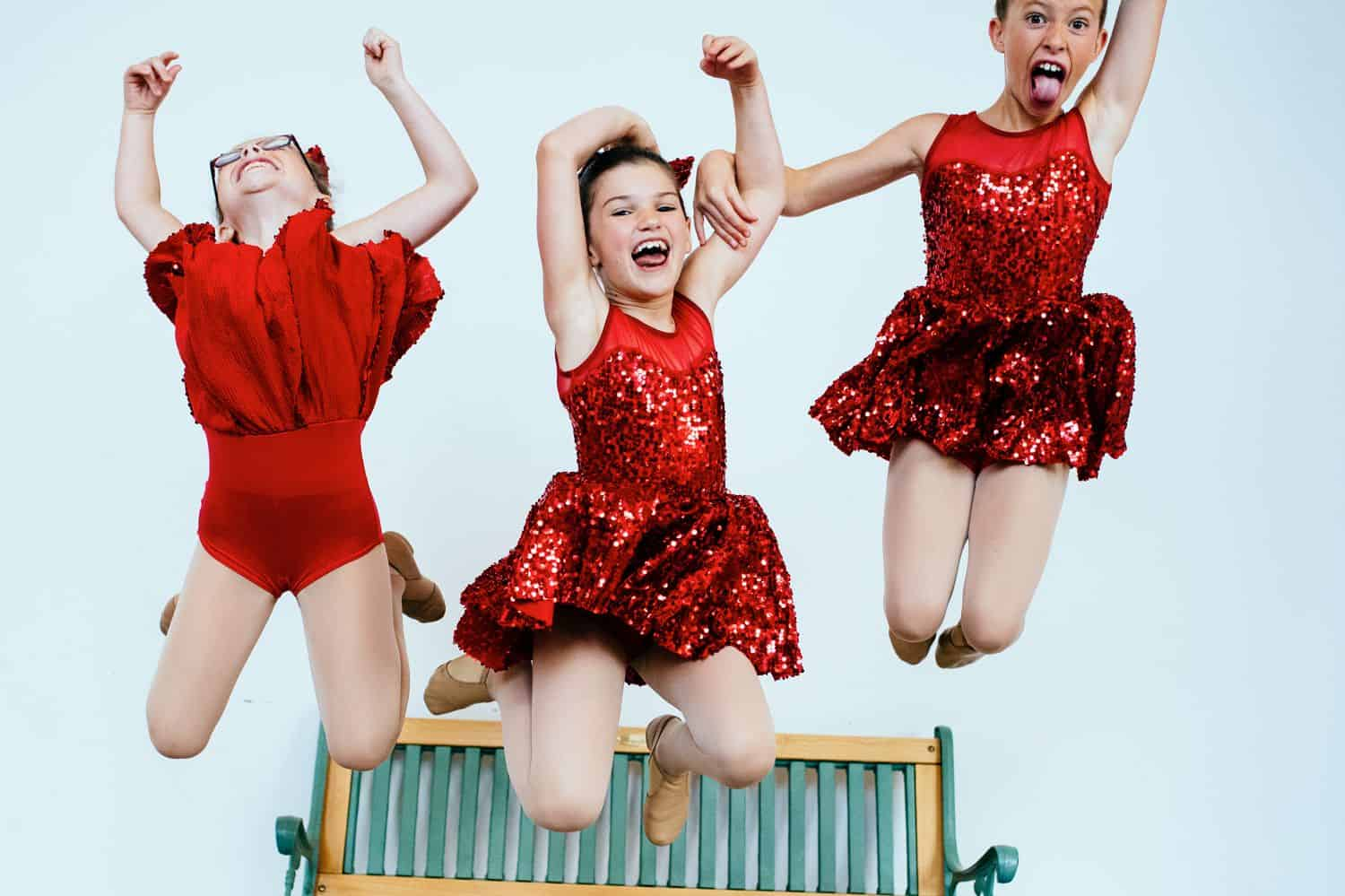Three little girls in red satin dresses leap into the air with their arms raised toward the sky. By Kate T. Parker for Strong is the New Pretty