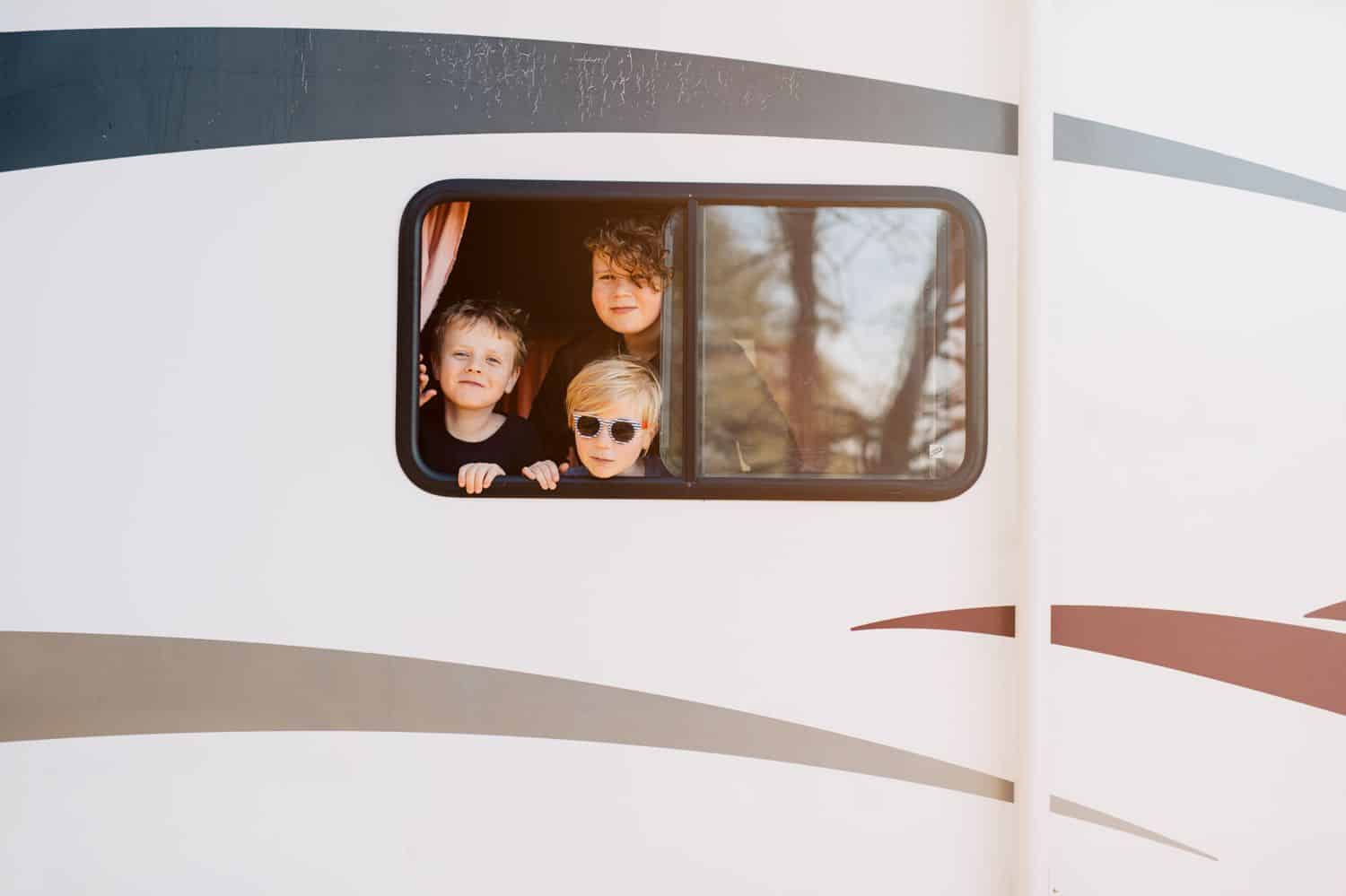 Three brothers look out the window of their RV. By Kate T. Parker for The Heart of a Boy