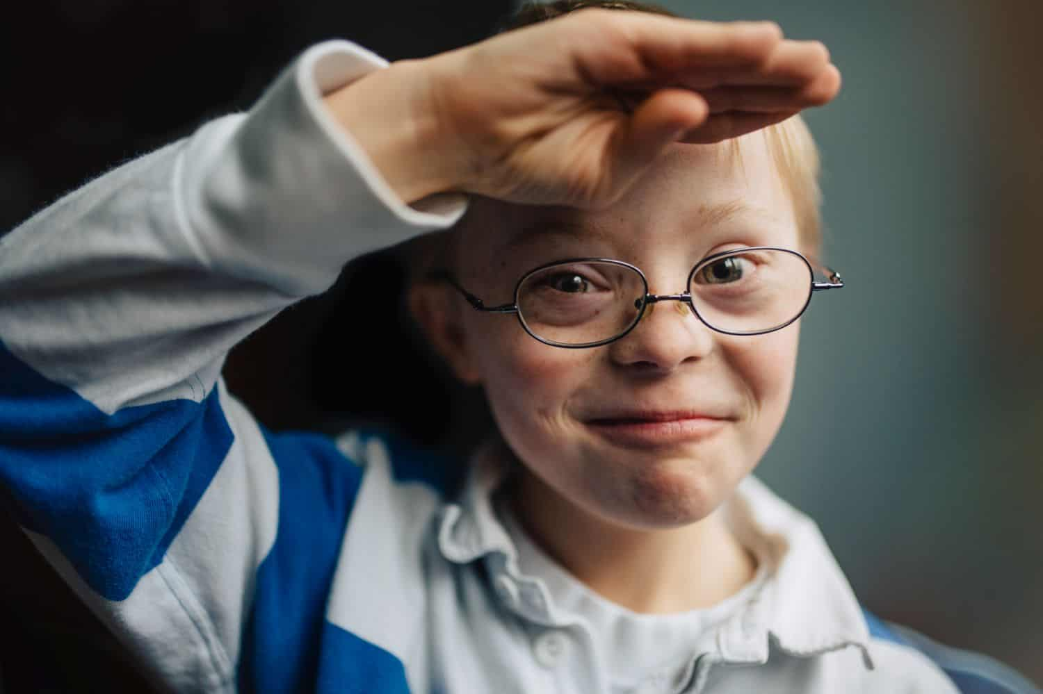 A little boy with Down syndrome grins and salutes Kate T. Parker's camera. Photographed for The Heart of a Boy