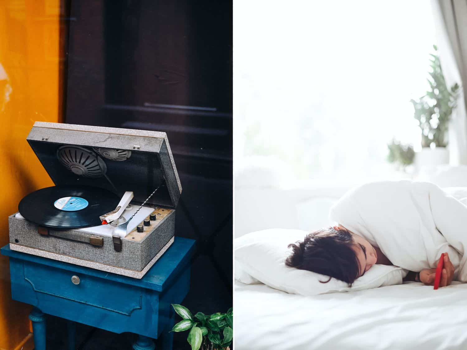 An open record player sits on a blue table by a yellow wall. A woman lies in a white bed looking at her smartphone.