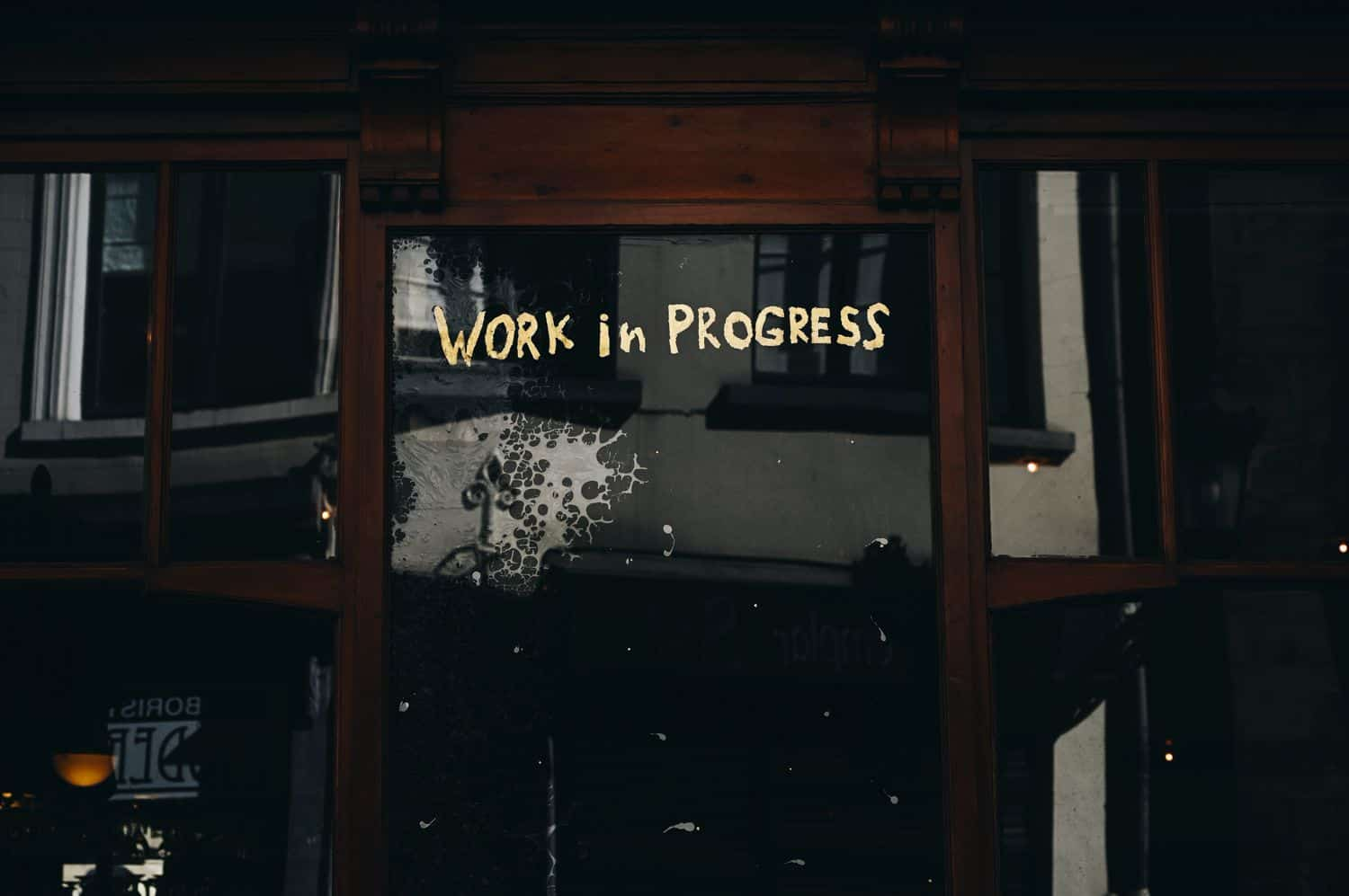 "A hand-painted gold-leaf sign on a shop window reads ""Work in Progress"". Part of ShootProof's ""Keep Calm & Photo On"" article photographed by Gaelle Marcel."