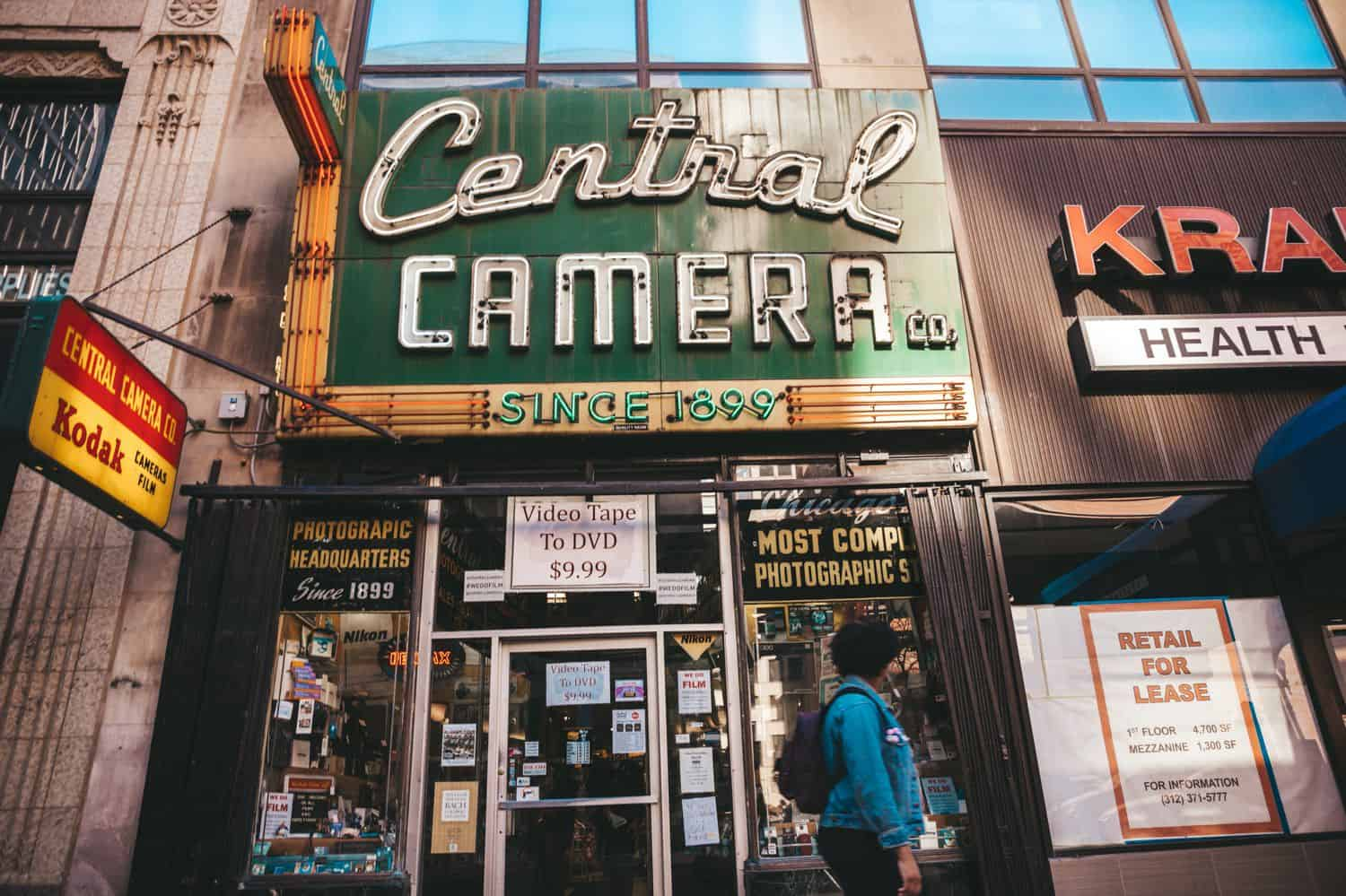 The Central Camera storefront is photographed with a person in a blue hoodie walking past.