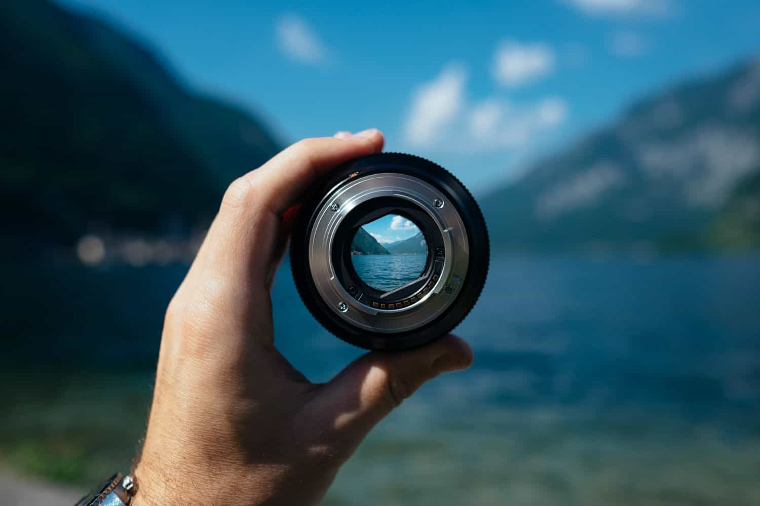 A person holds a lens separate from the camera. You can see beautiful blue sky, mountains, and a lake through the lens.