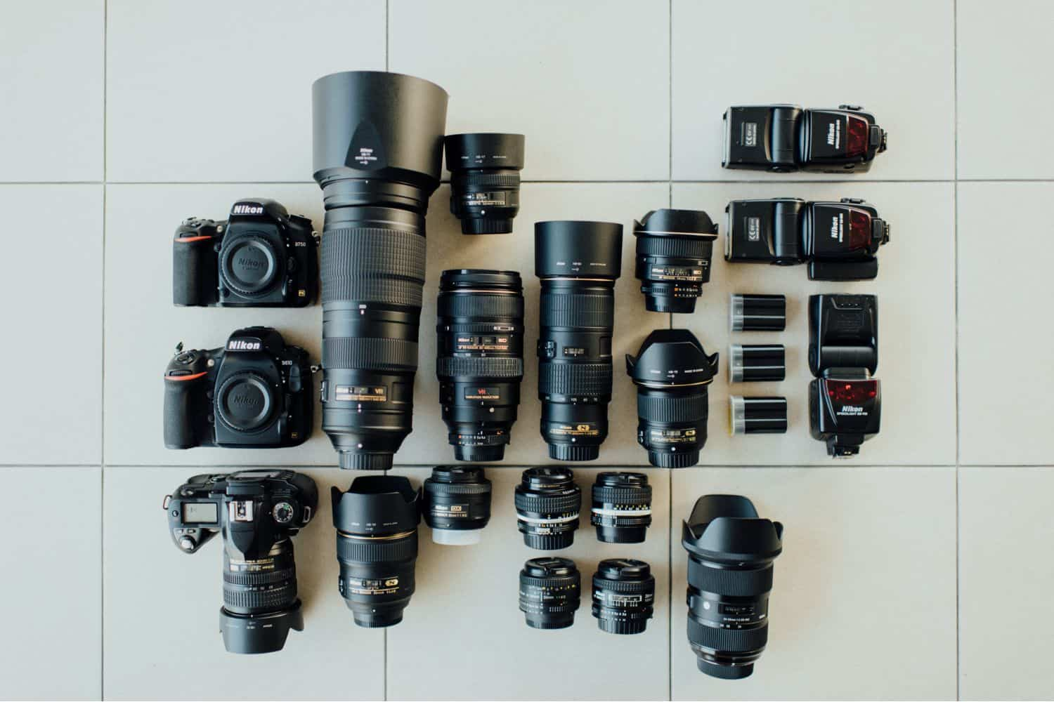A collection of used camera lenses is laid out on a linoleum floor.