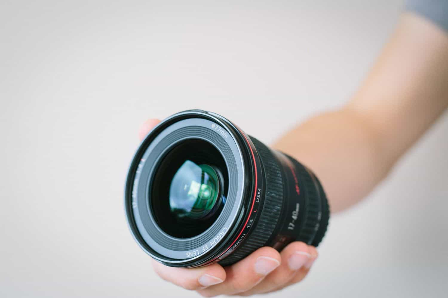 Someone holds a wide angle lens in front of a white wall.