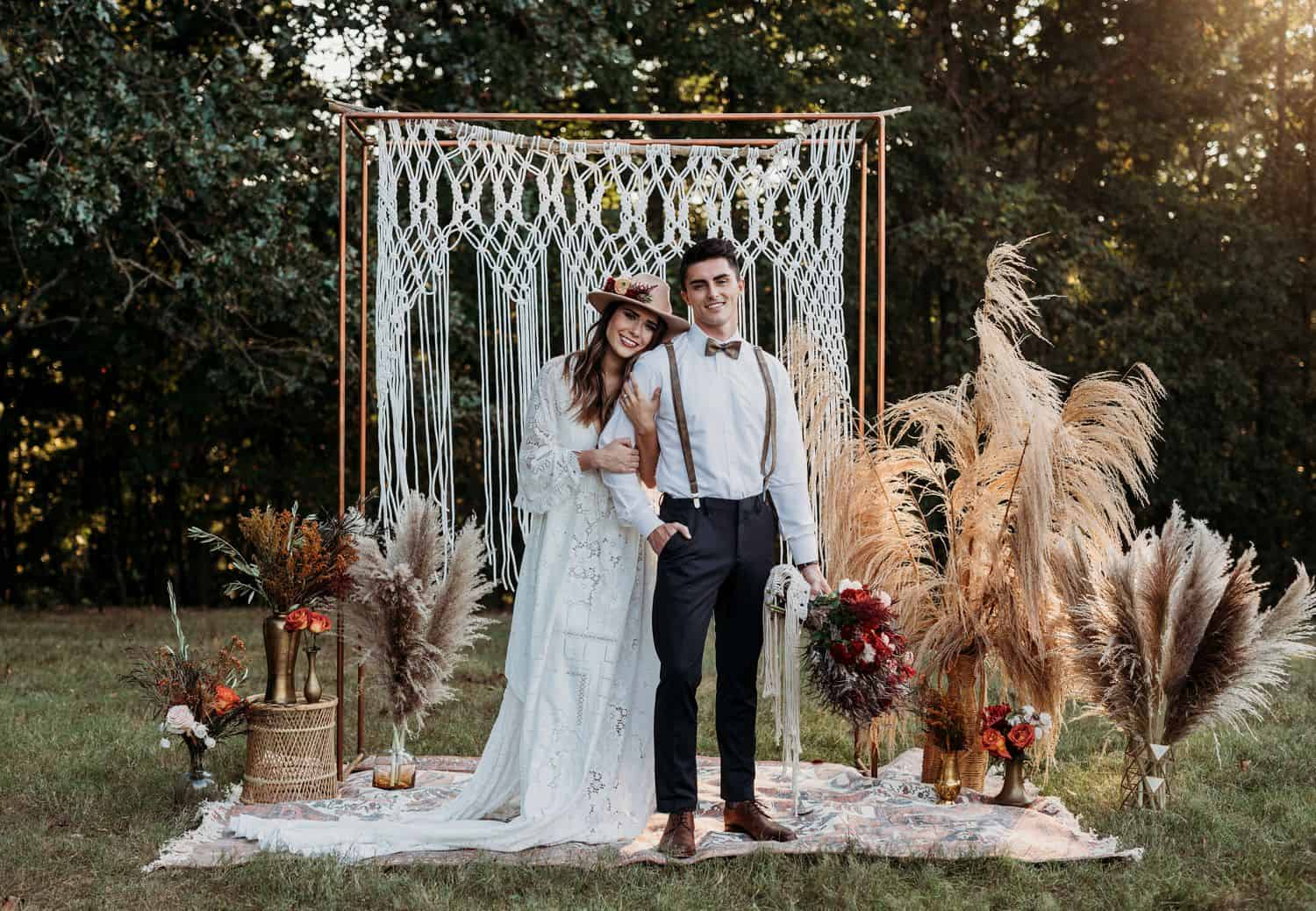 Boho bride and groom pose in front of a macrame backdrop