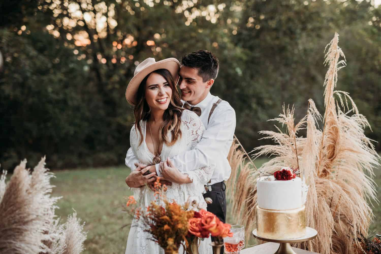 A boho bride and groom hug each other in front of their cake table