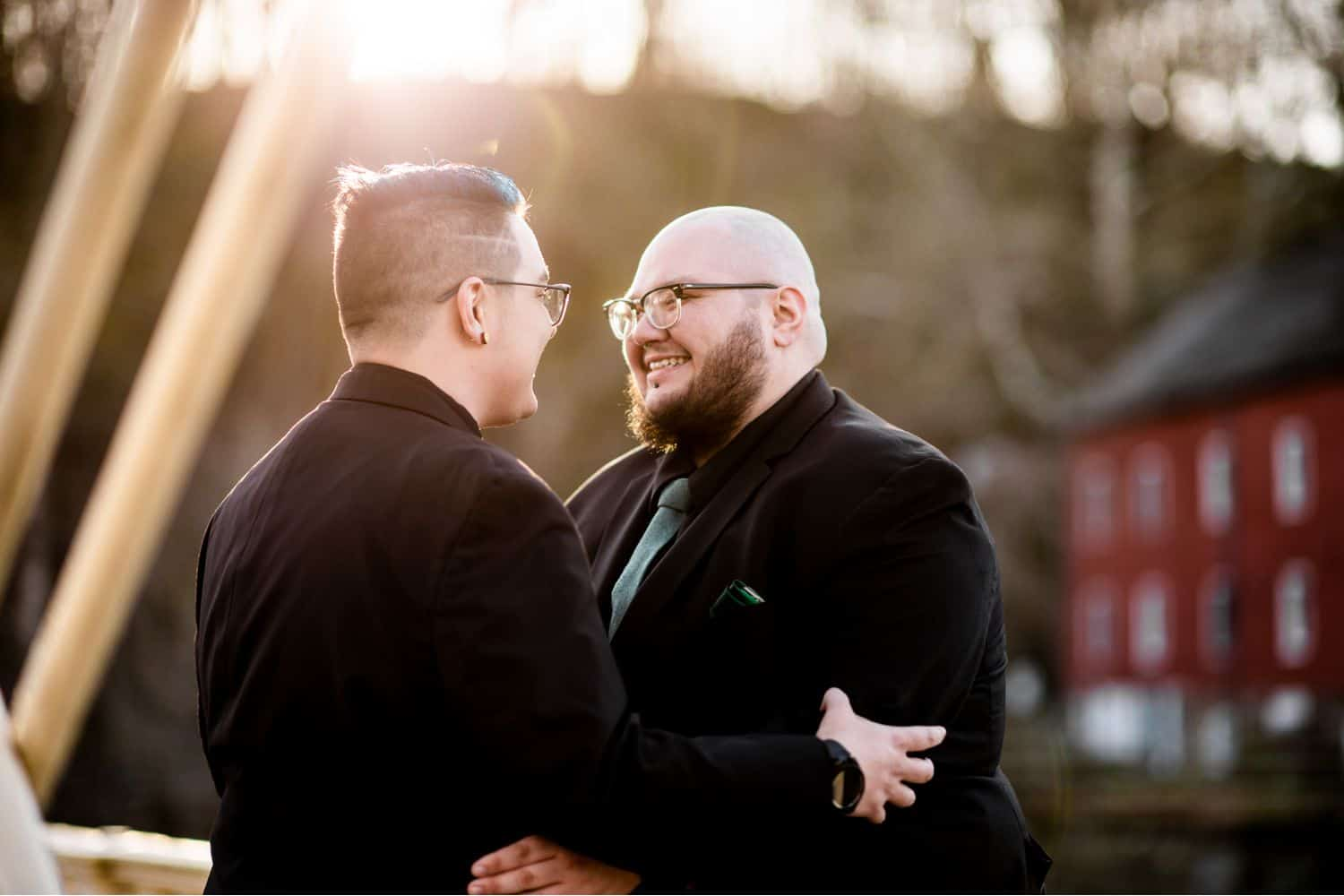 Two husbands hold one another and smile as sunlight spills onto them from behind