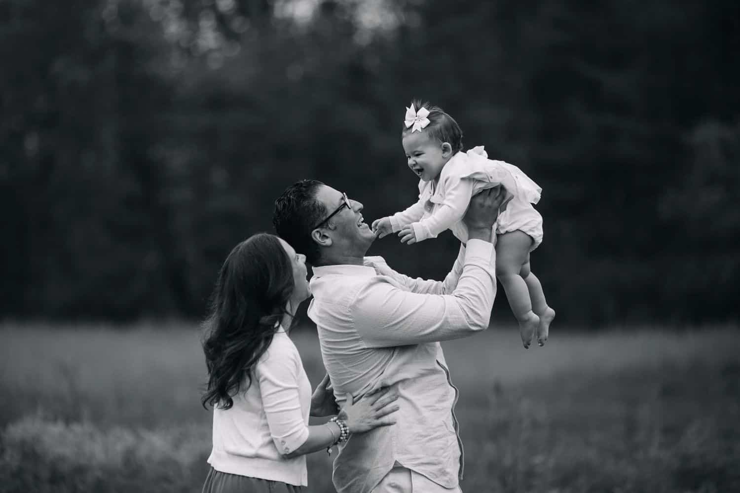 Black and white portrait of two parents lifting their baby daughter into the air