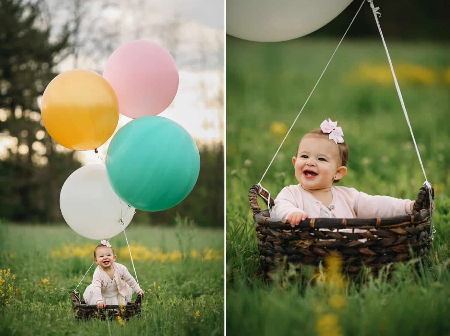 A toddler girl sits in a field in a basket surrounded by giant balloons