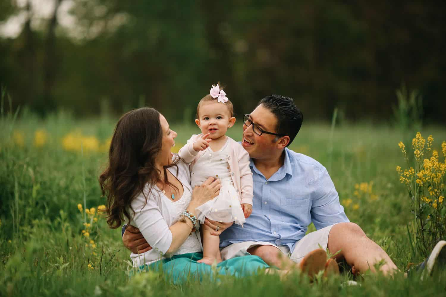 Two parents sit in a field on either side of their tiny daughter