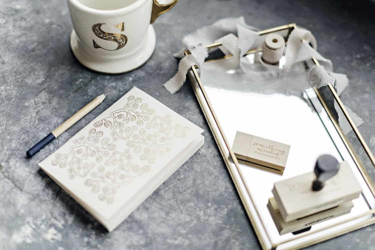 A gray marbled workspace is laid out with a journal, coffee mug, and other desk accessories