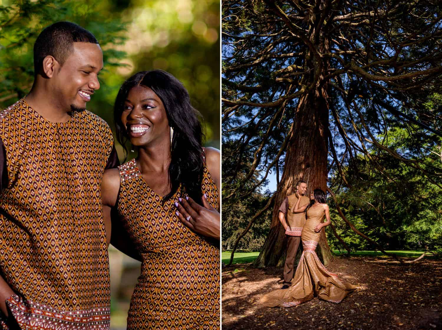 A Black couple poses in traditional African attire in front of a massive tree