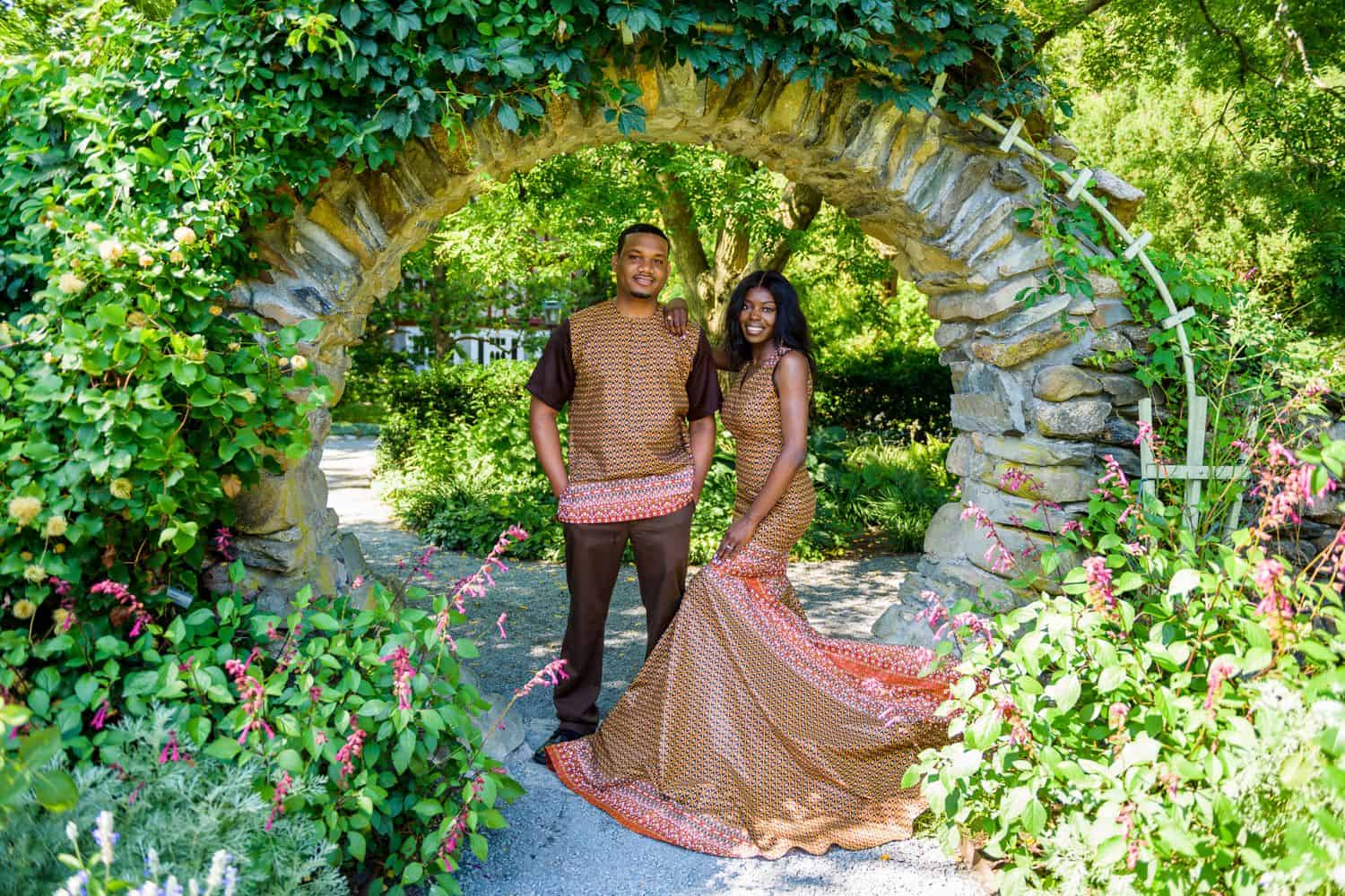 A Black couples poses in an ivy-covered archway wearing traditional African clothing