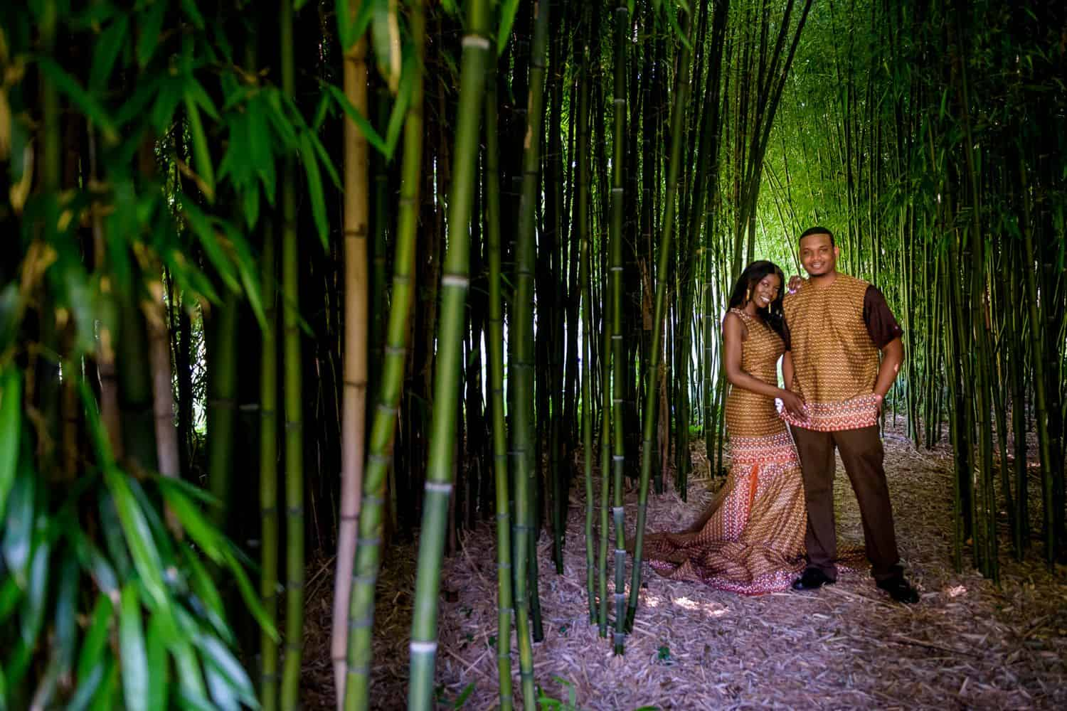 A Black couple poses wearing traditional African attire surrounded by towering bamboo shoots