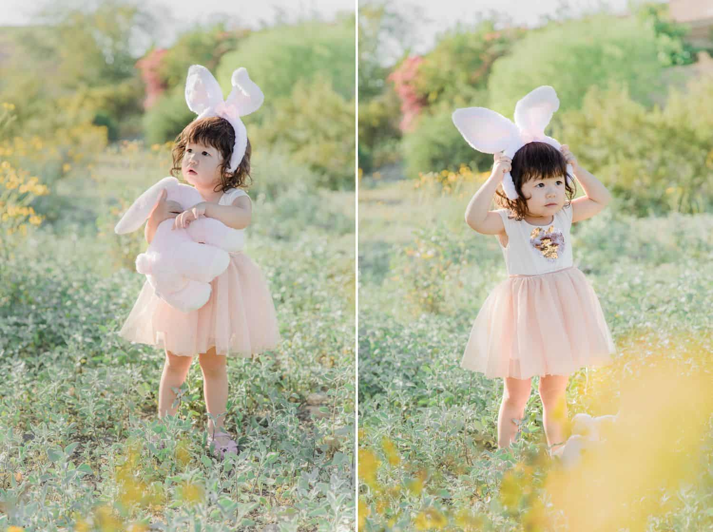 A little girl in a pink dress stands in a field wearing bunny ears