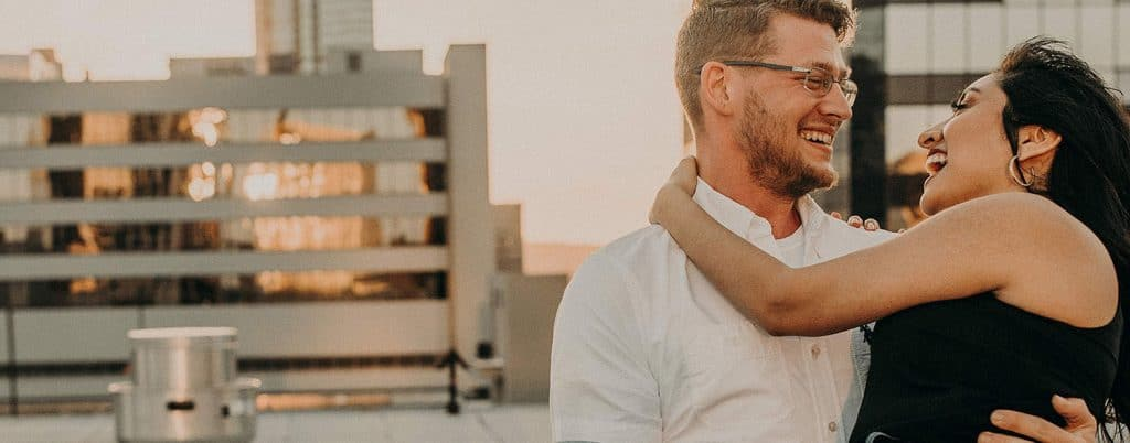 An engaged couple embraces on a rooftop overlooking the city skyline