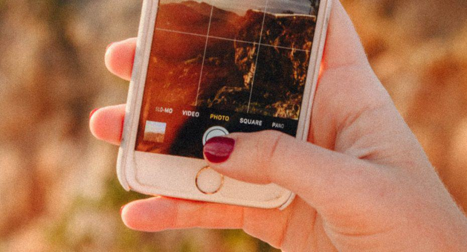 A woman's hand holding an iPhone and taking a picture of the coastal landscape