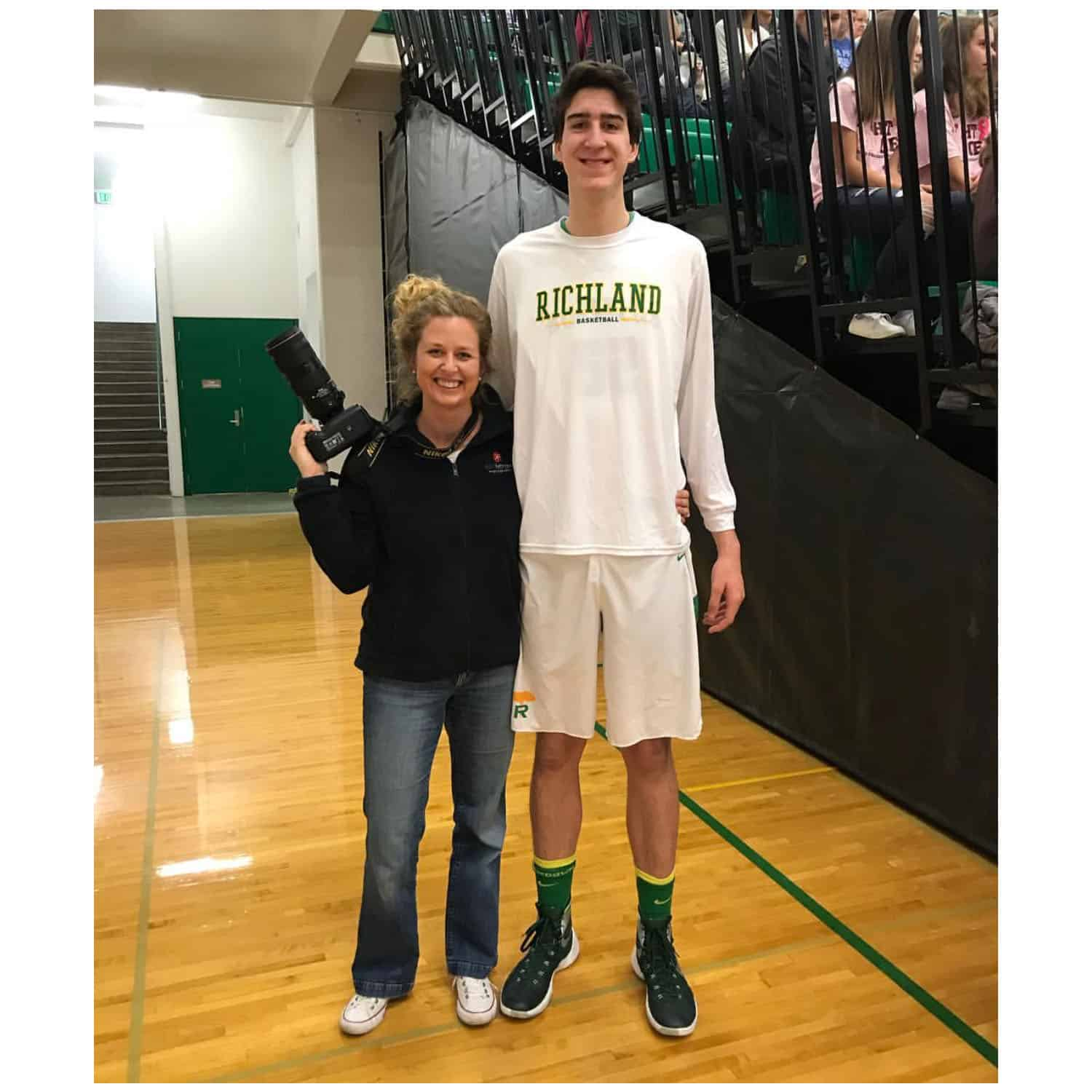 "5'10"" photographer Kim Fetrow stands beside varsity player Riley Sorn, 7'4"""