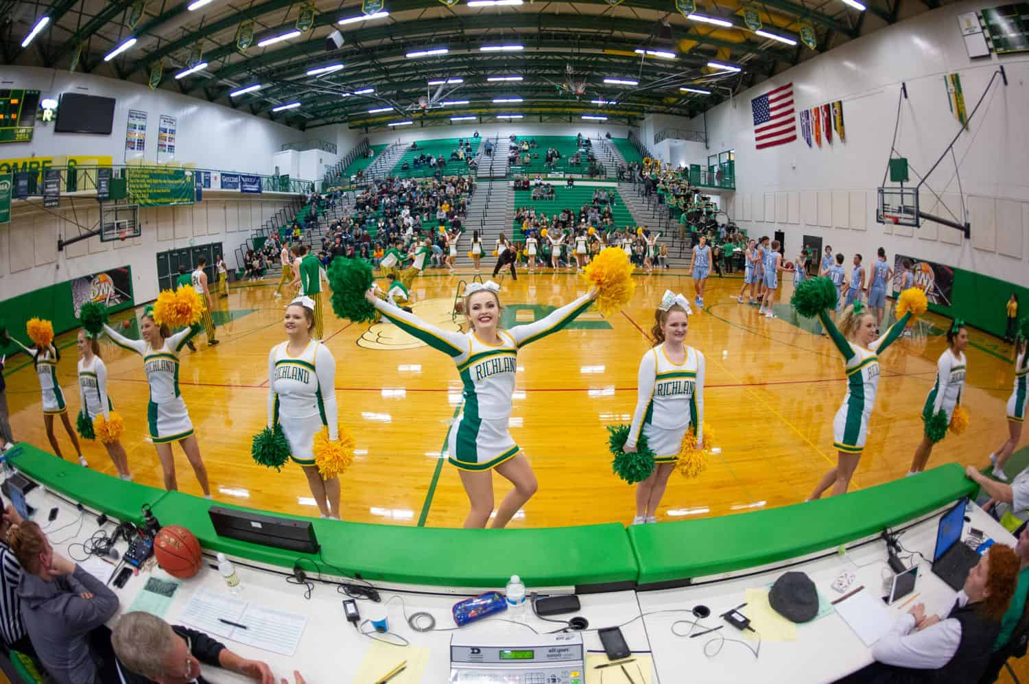A wide angle lens helps photographer Kim Fetrow capture this image of cheerleaders at a high school basketball game