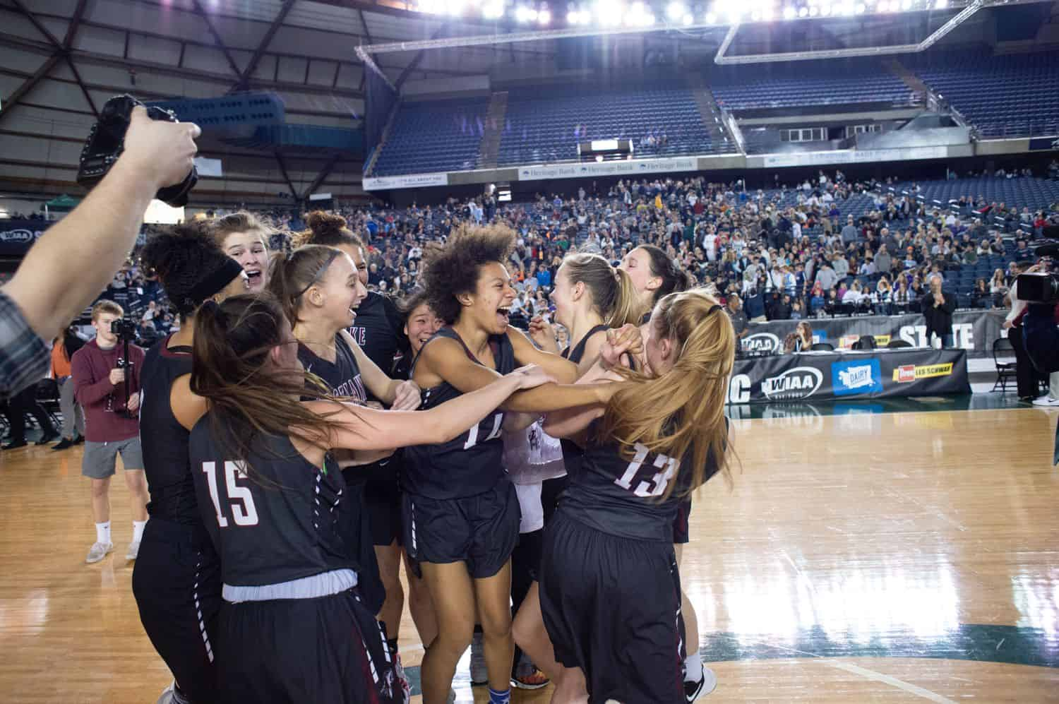 A group of high school girl basketball players celebrate their win on the court